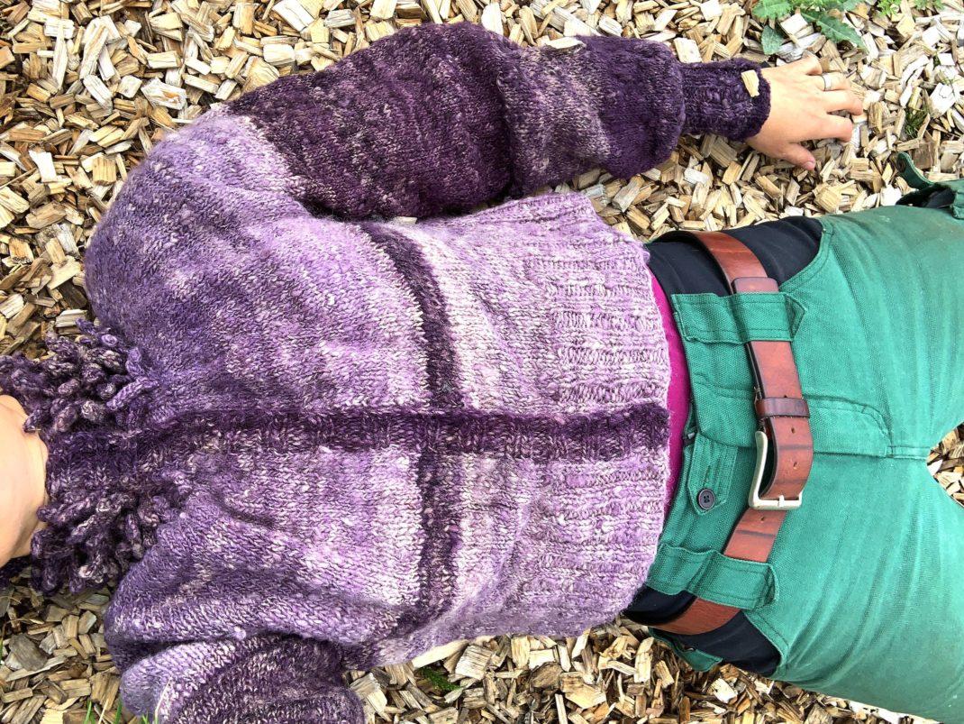 Sara ligger på träflis och hela tröjan syns.