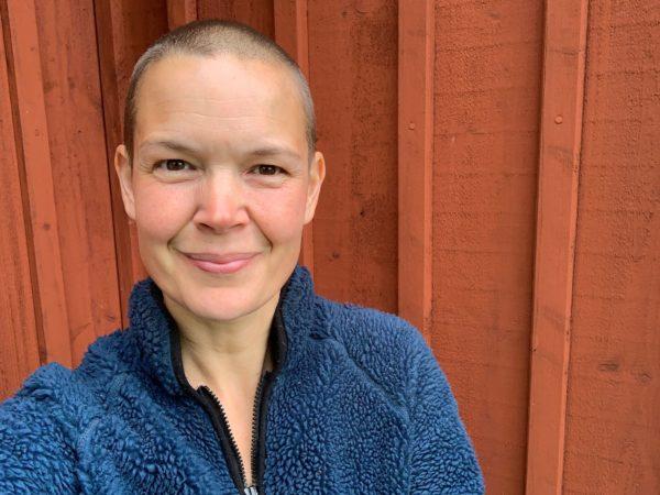 Sara i blå tröja mot en faluröd trävägg.