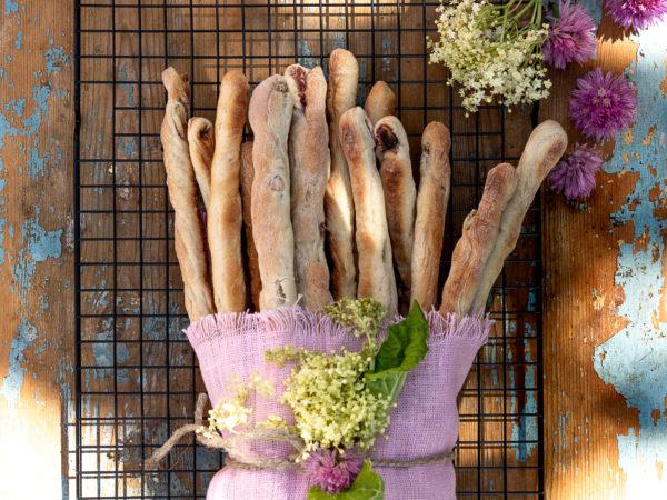 Fina brödpinnar med rabarber och kardemumma i en lila handduk.