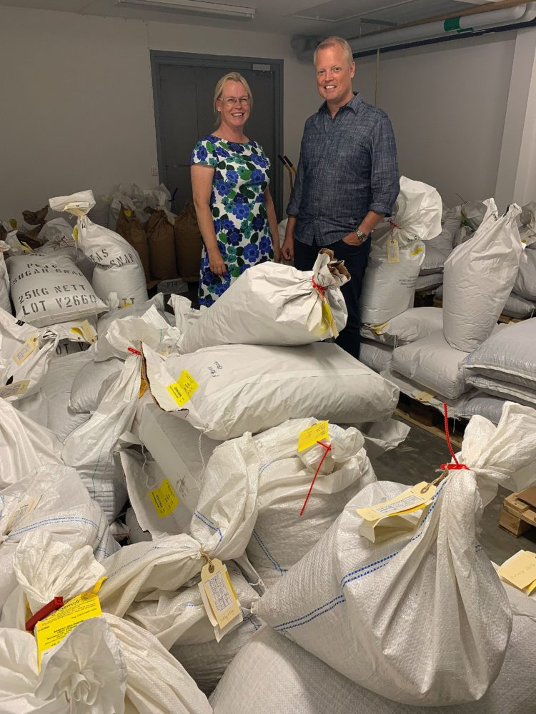 Två personer står i ett rum med massor av stora vita säckar.