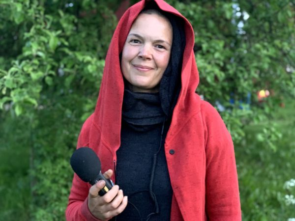 Sara Bäckmo står i trädgården i röd luvtröja och bandare i handen.