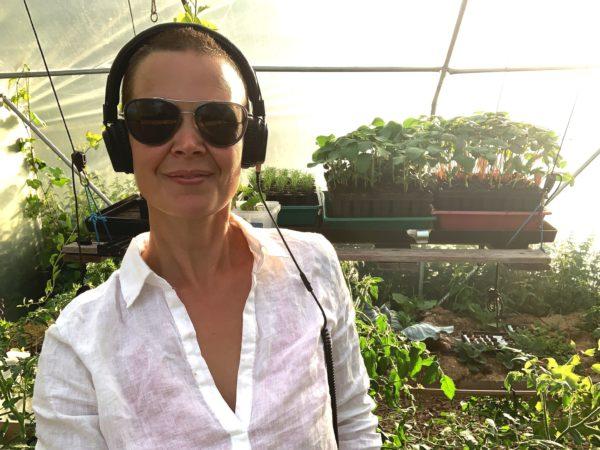 Sara står i vit skjorta i kvällsljus, solglasögon och hörlurar, i tunnelväxthuset.