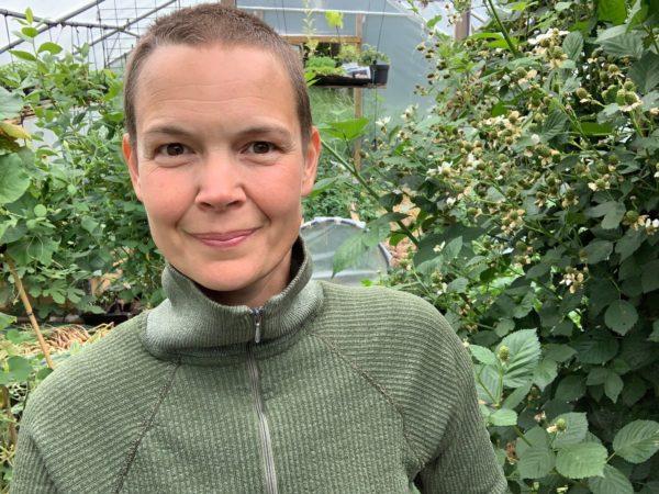 Sara i grön tröja i sitt gröna växthus.