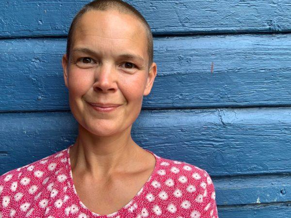 Sara mot en fin blå vägg.
