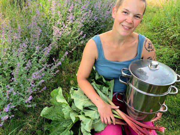 Sara sitter med en saftmaja och rabarber i trädgården vid lila blommor.
