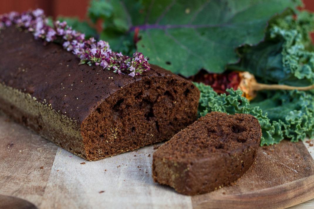 En saftig mörkbrun chokladkaka ligger på ett bord bredvid grönkål.