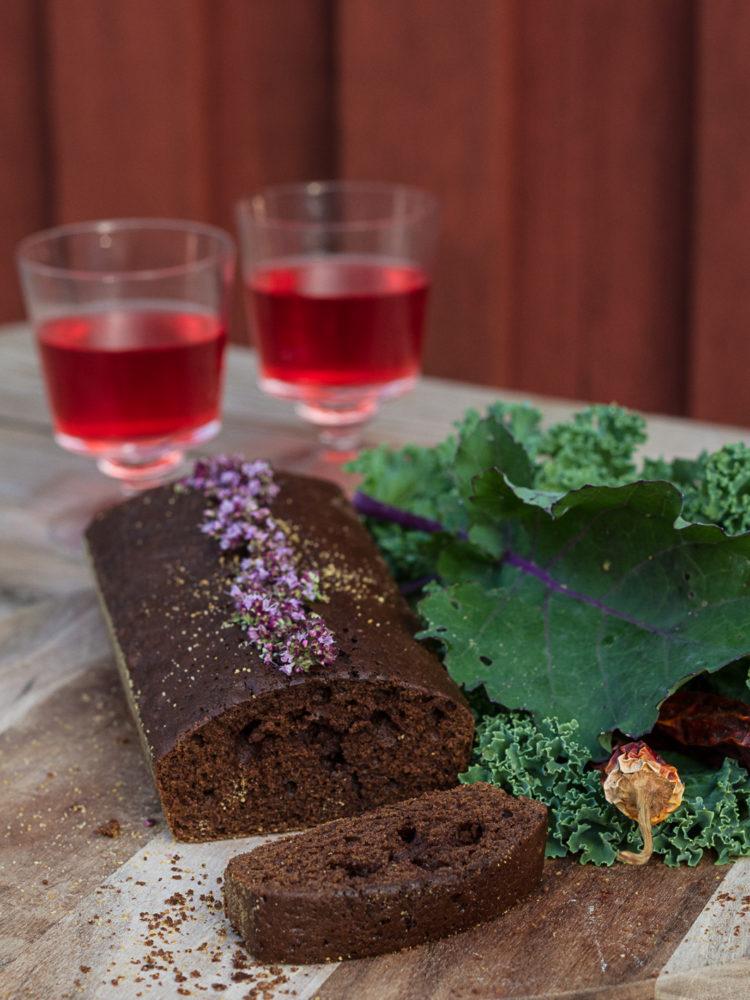 En saftig mörkbrun chokladkaka ligger på ett bord bredvid grönkål och två glas vinbärssaft.
