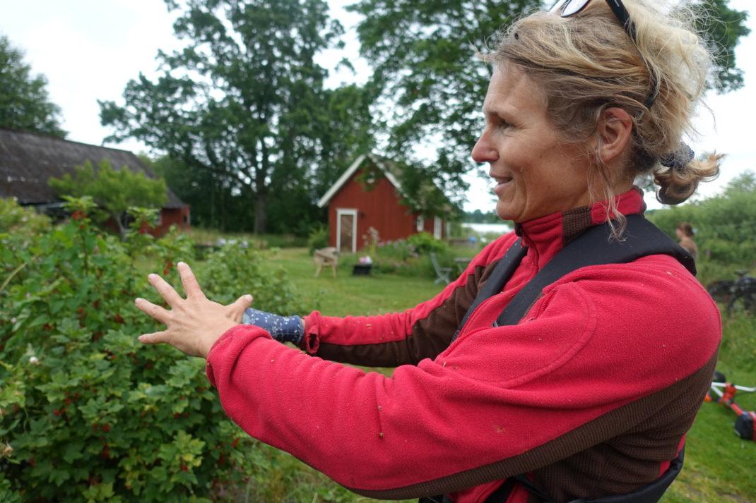 En kvinna i röd fleecetröja står och gestikulerar.