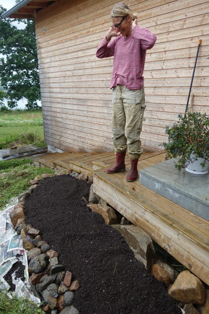 En kvinna står på ett träfärgat däck och tittar ner på en liten jordplätt.