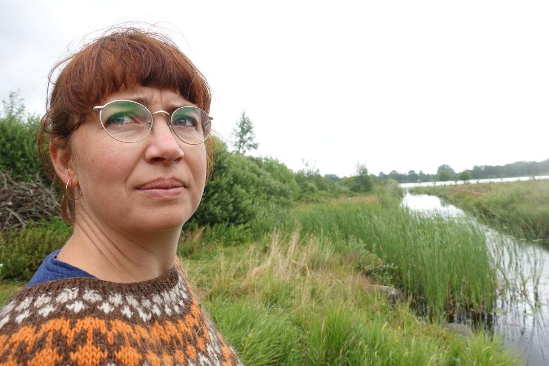 En kvinna står vid en sjö.