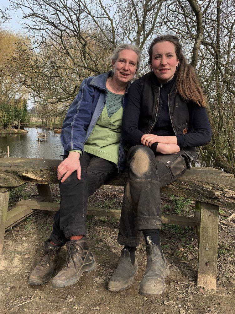 Två kvinnor sitter på en bänk med en damm i bakgrunden.