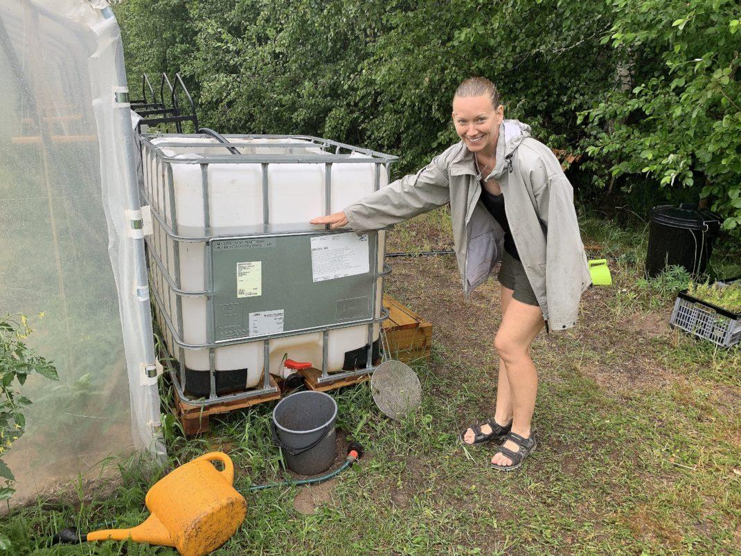 En tjej visar med handen vattennivån i en stor vit vattentank.