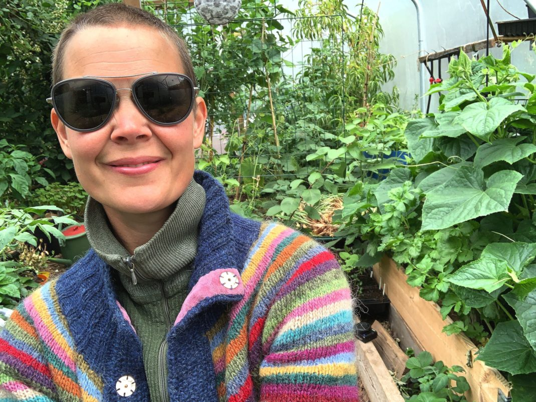 Sara fotograferad i tunnelväxthuset i randig kofta och solglasögon