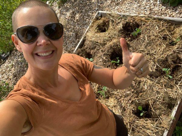 Sara vid en nyplanterad låda i trädgården.