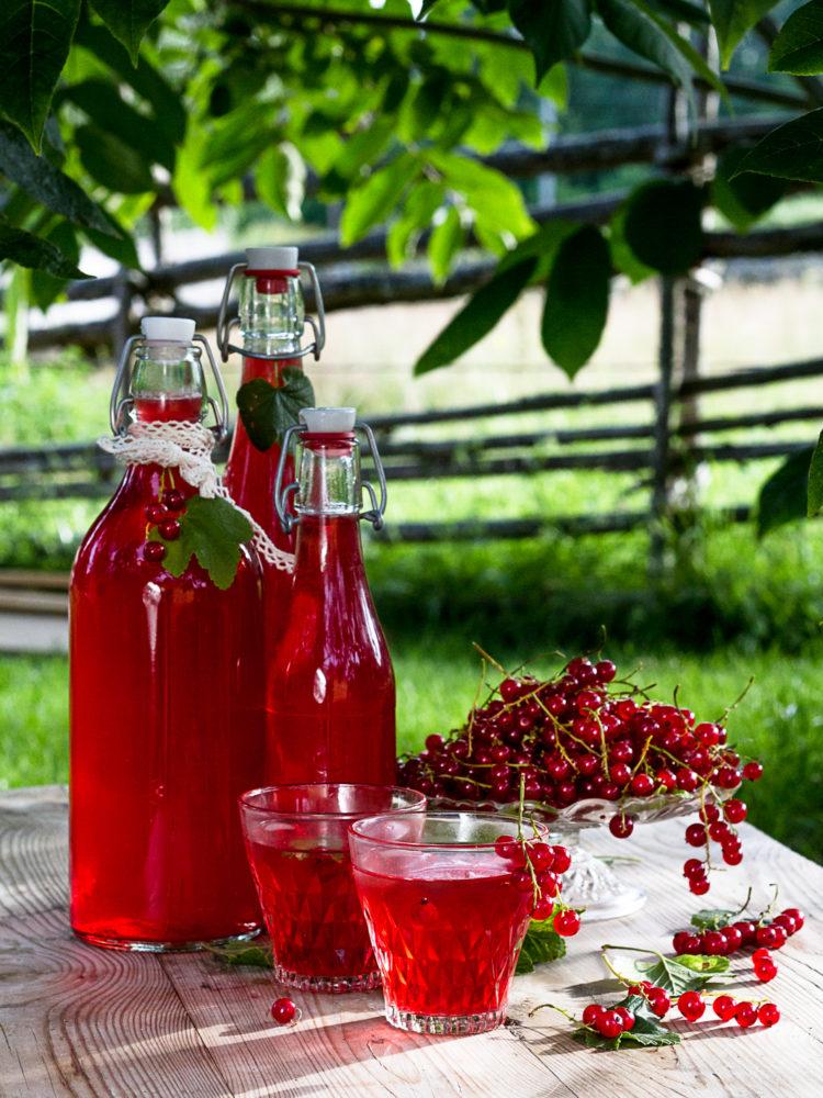 Läcker röd saft av vinbär i fina glaskflaskor.