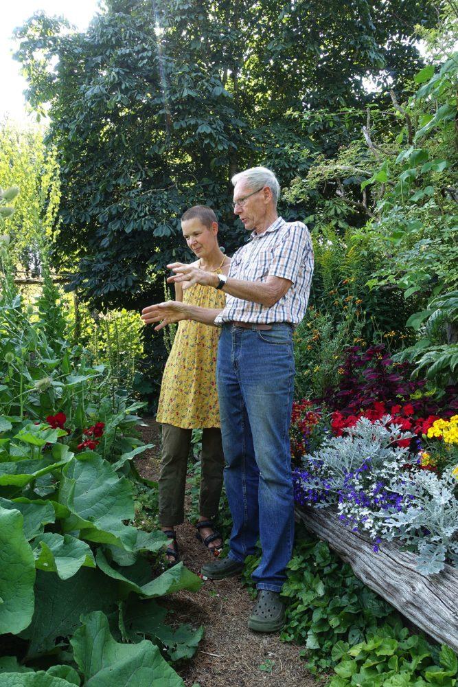En kvinna i gul klänning och en äldre man i jeans och skjorta står i en trädgård och diskuterar.