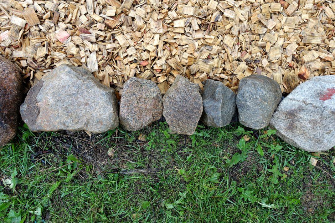 En kant av stora grå stenar i mitten av bilden, träflis i övre delen och gräs nedanför kanten.