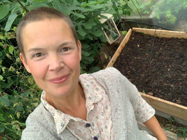Sara i växthuset vid en pallkrage med frilagd jord.