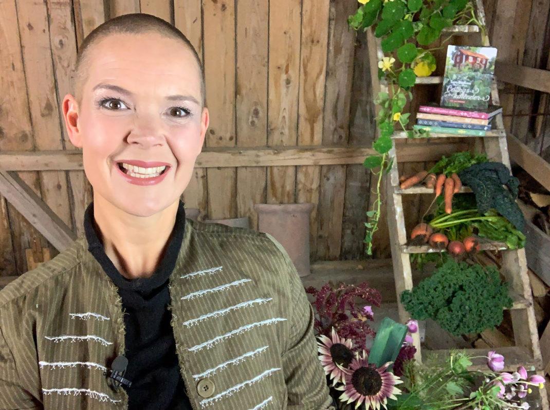 Sara håller ett föredrag om sina första odlarår. Hon står i en lada framför sina böcker och grönsaker och ser glad ut.