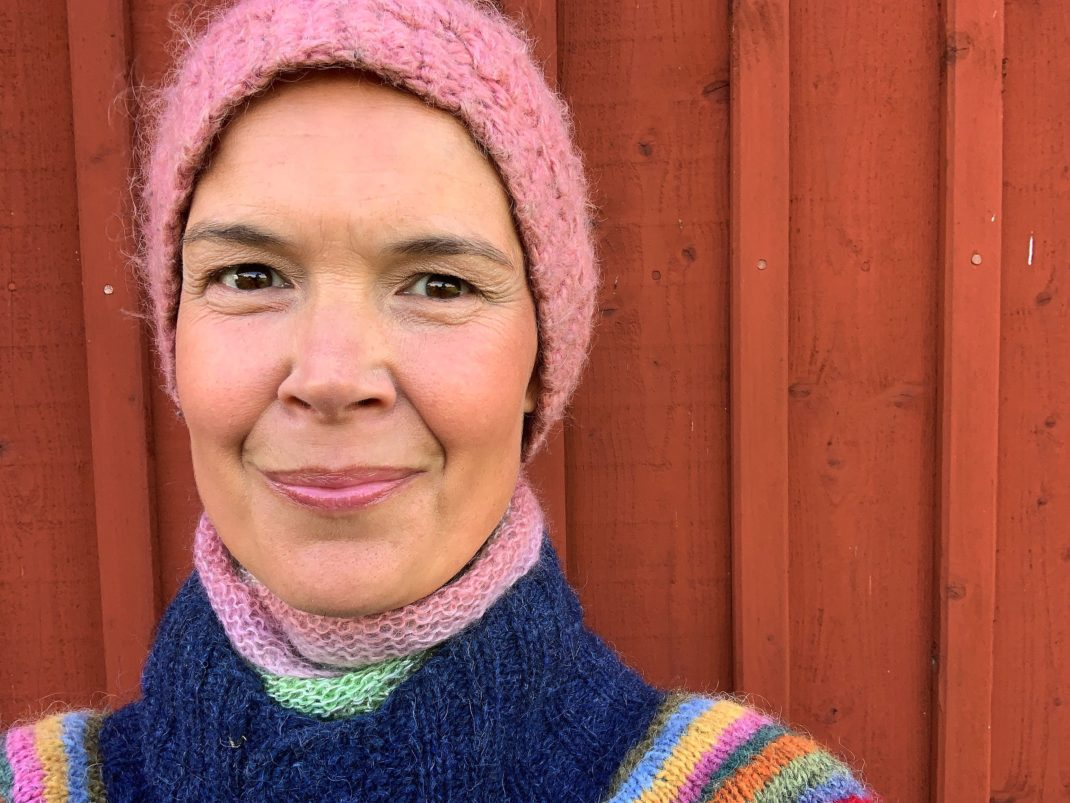 Porträttbild på Sara i rosa mössa och färgglad kofta.