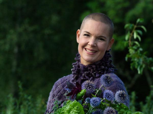 Porträttbild av Sara i lila kofta och en bukett blå blommor i famnen.
