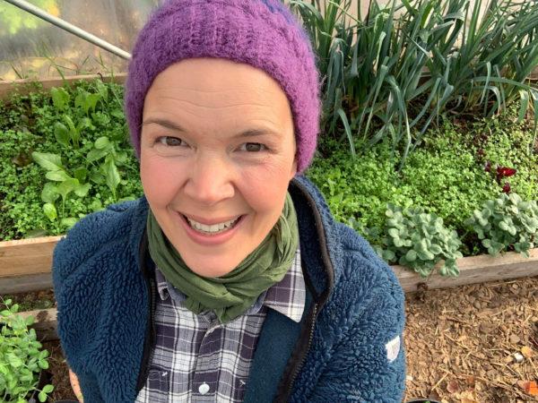 En glad Sara i ett grönt prunkande tunnelväxthus