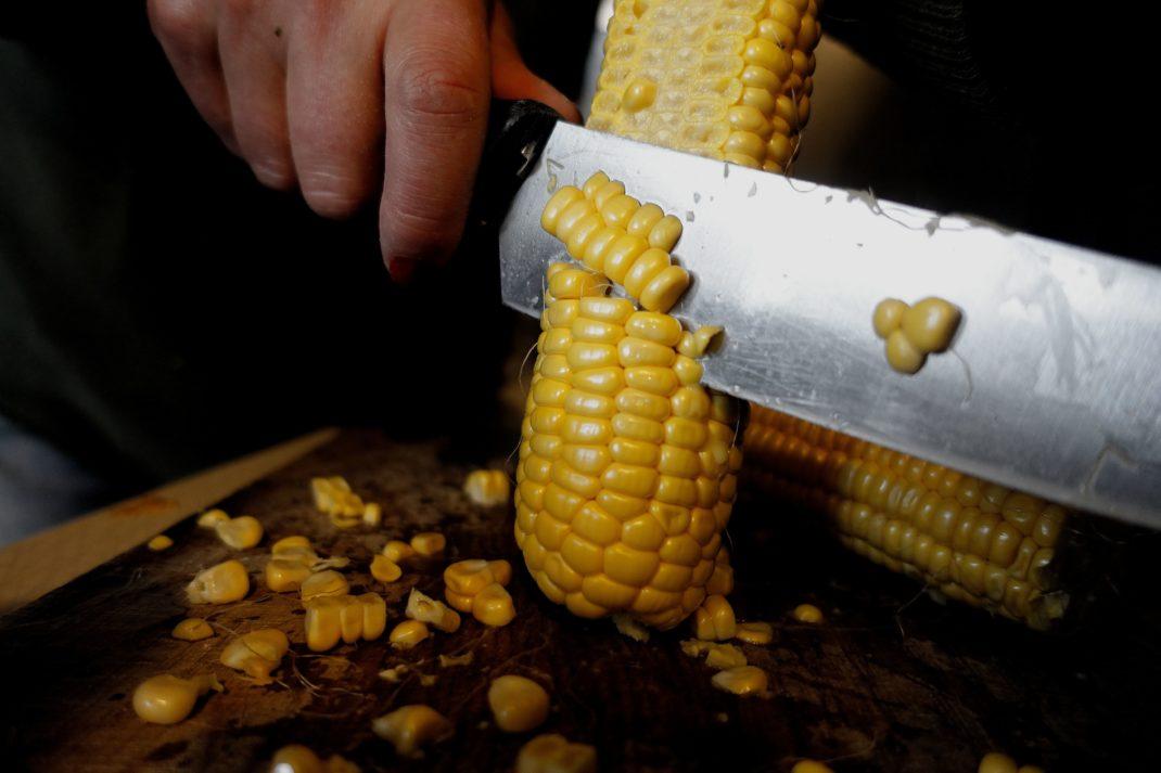 En kniv skär av korn från kolven.