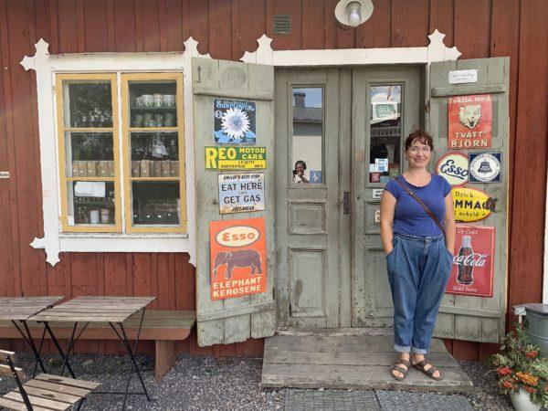 En kvinna i blått står framför en gammal lanthandel.