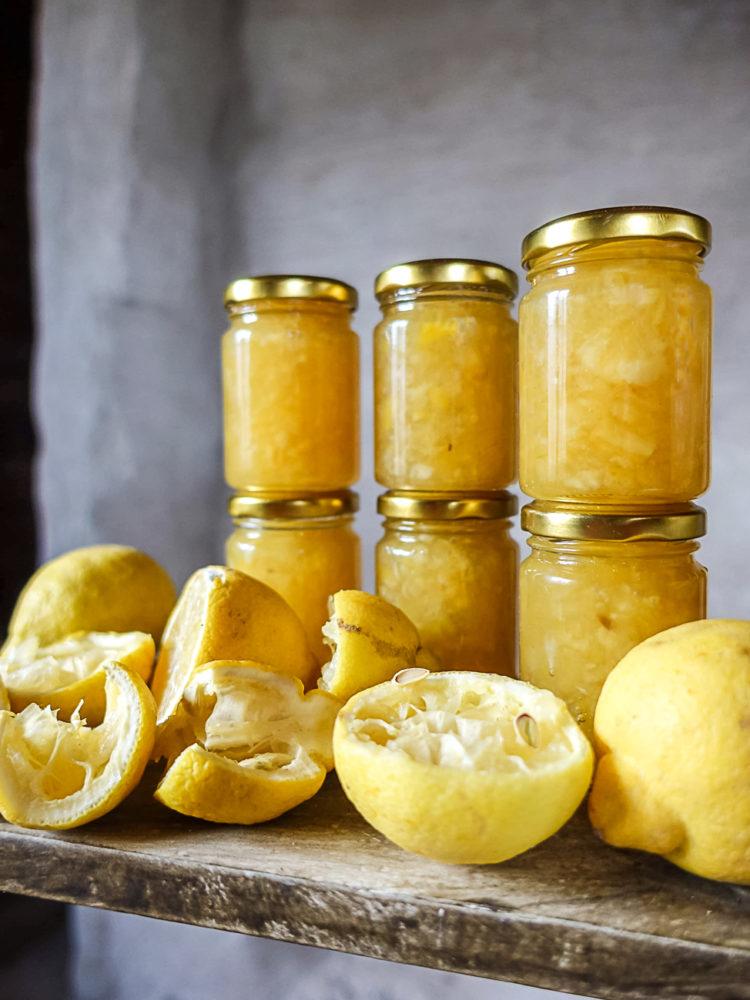 Glasburkar med citronmarmelad och citroner