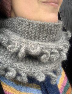 Sara har på sig en vacker, grå stickad halskrage.