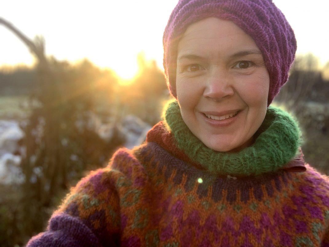 En selfie av Sara i stickat i motljus.
