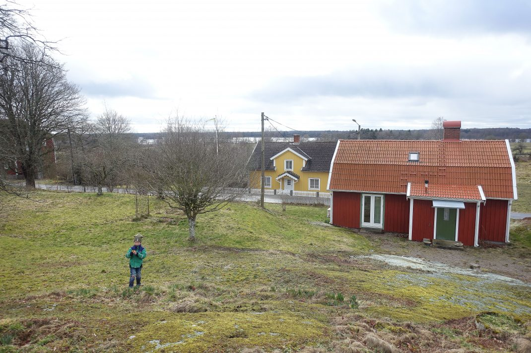 Foto taget från en bergknalle med utsikt över en röd stuga.