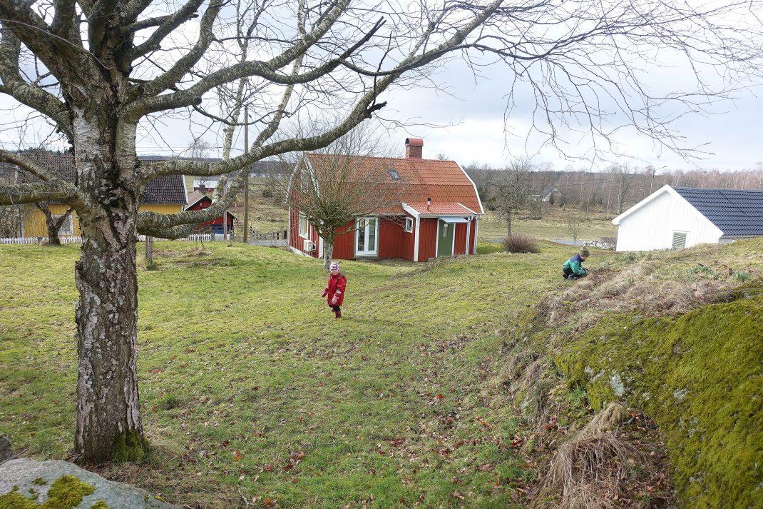 En sluttande gräsmatta nedanför ett berg, längst ner ett rött litet hus.