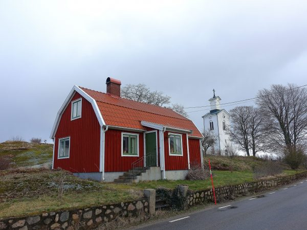 Ett litet rött hus med stenmur framför och en vit kyrka i bakgrunden.