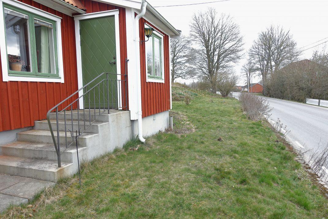Ett rött hus med sliten gräsmatta framför.