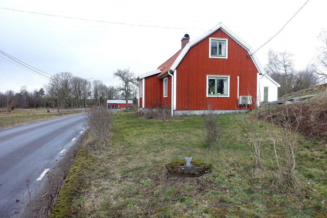 En skruttig gräsmatta framför en röd liten stuga.