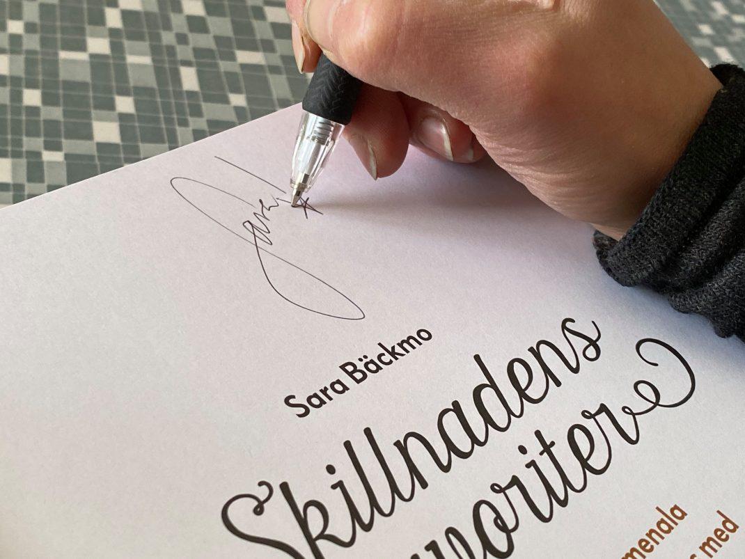 Sara signerar.