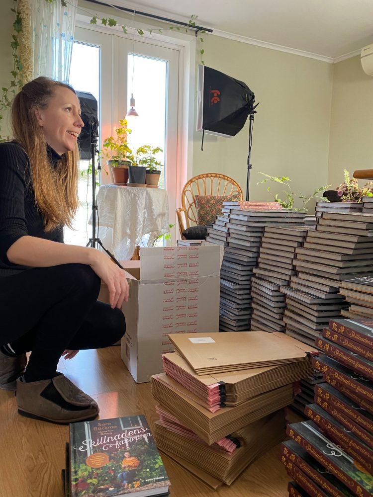 En kvinna sitter på knä på golvet bland högar av böcker.