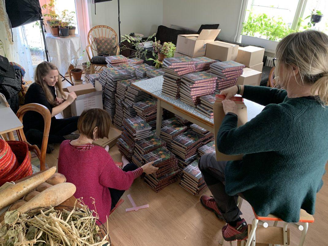 Kvinnor sitter på golvet bland högar med böcker.