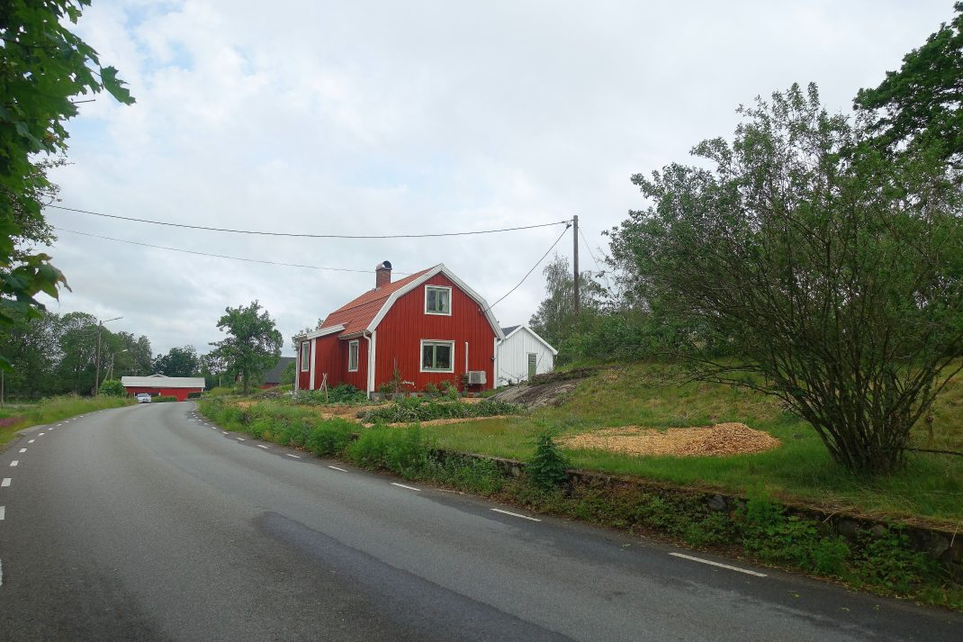 Ett rött hus ligger alldeles vid en asfaltsväg.