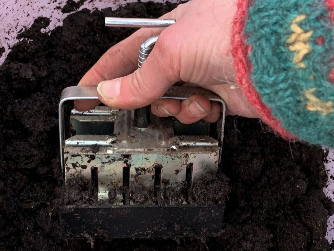 Redskapet trycks ner i en svart jordmassa.