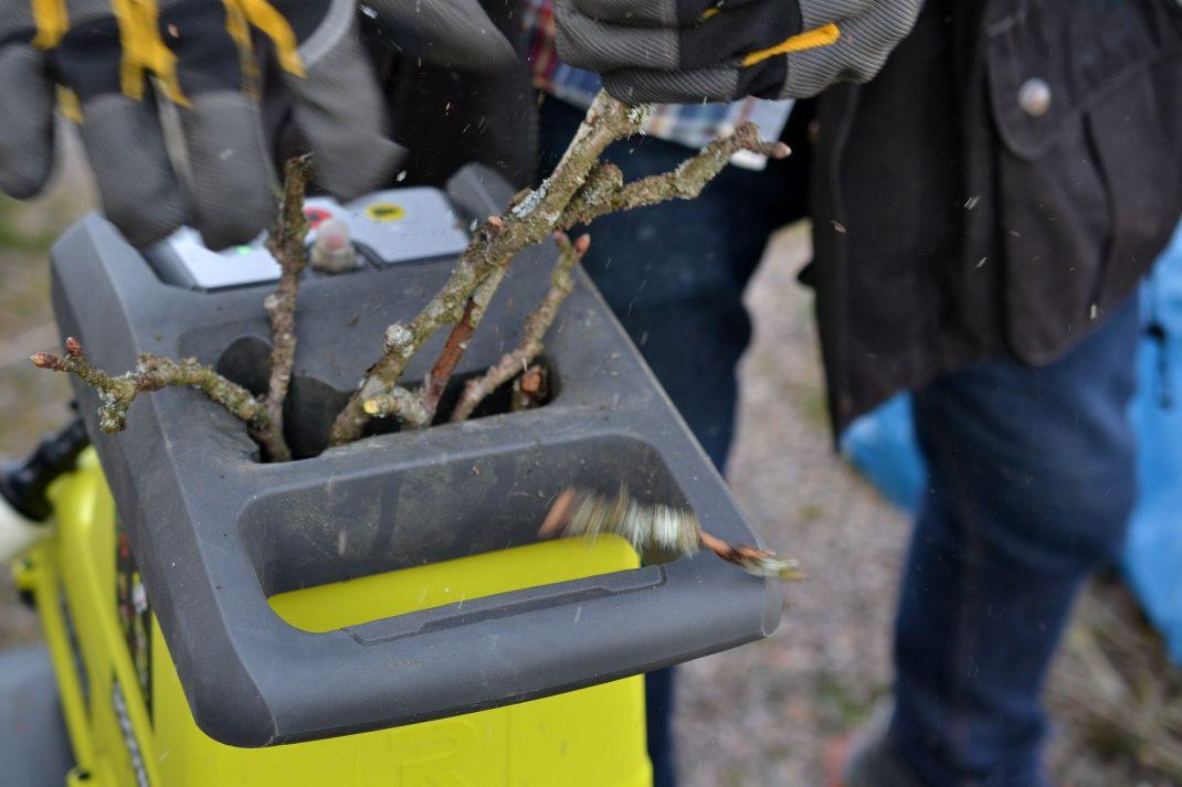 Närbild på händer som trycker ner pinnar i kompostkvarnen.