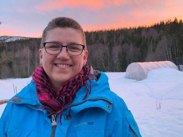 En kvinna i blå jacka står i en magisk solnedgång i vinterlandskap.
