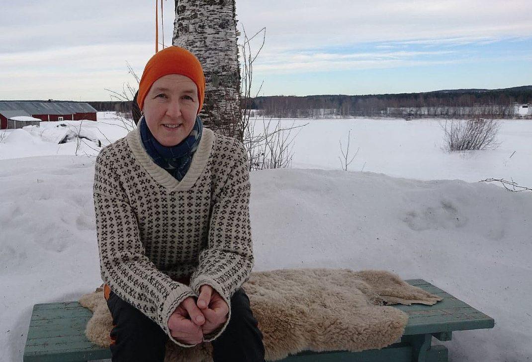 En kvinna sitter vid en björk i vintrigt landskap.