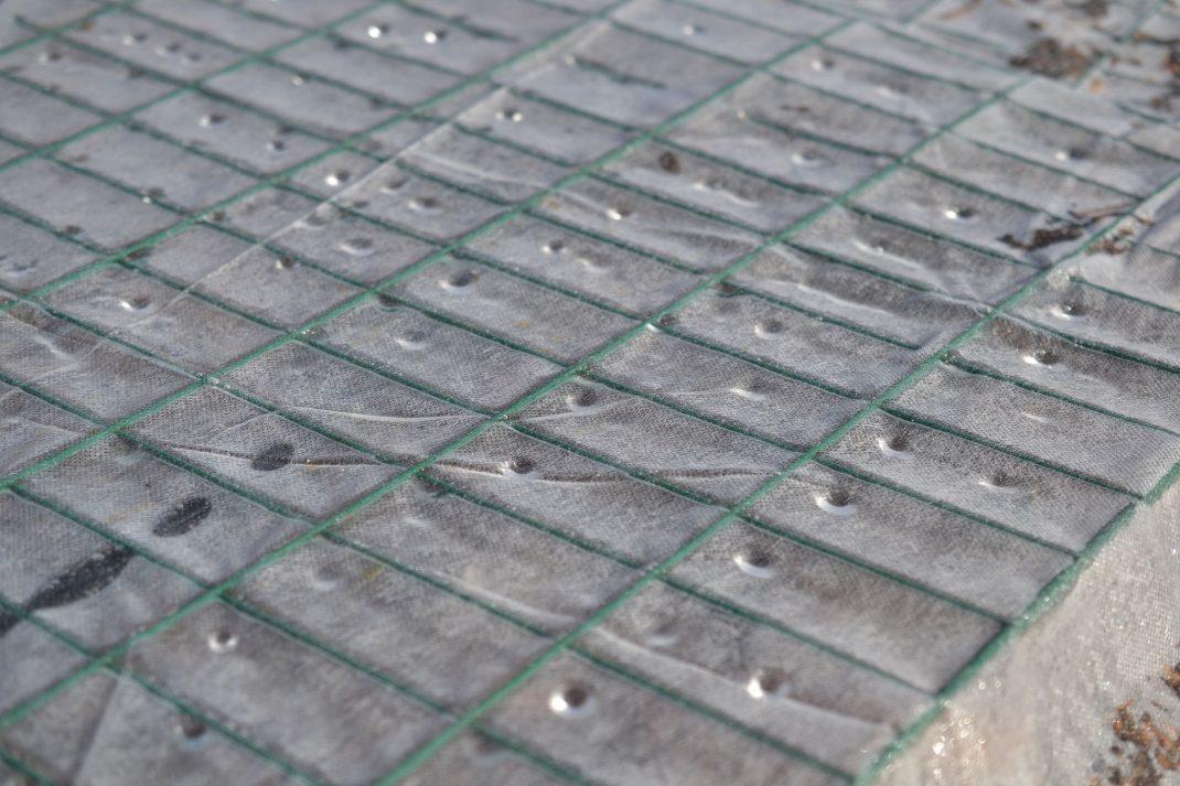 Fiberduk över kompostgaller med små vattendroppar.
