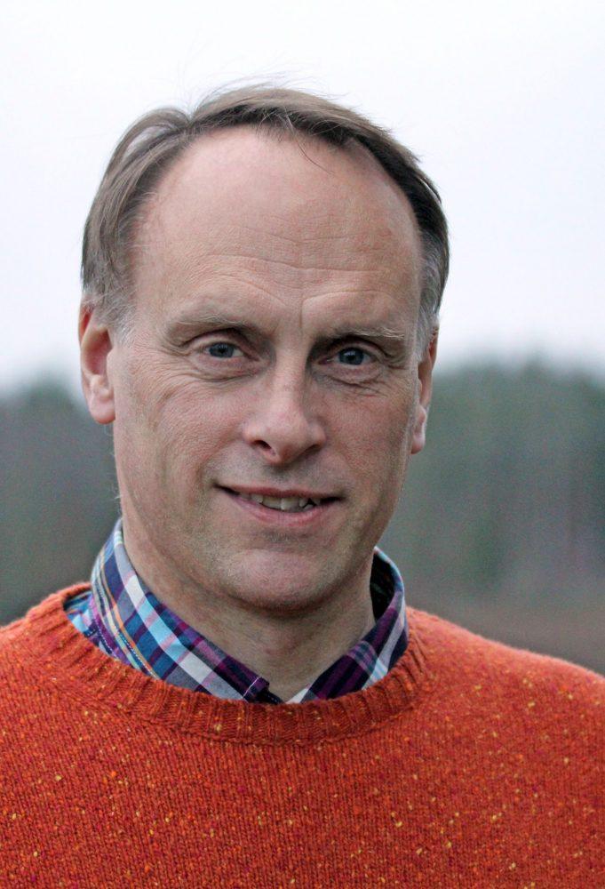 Porträttfoto på en man i orange tröja