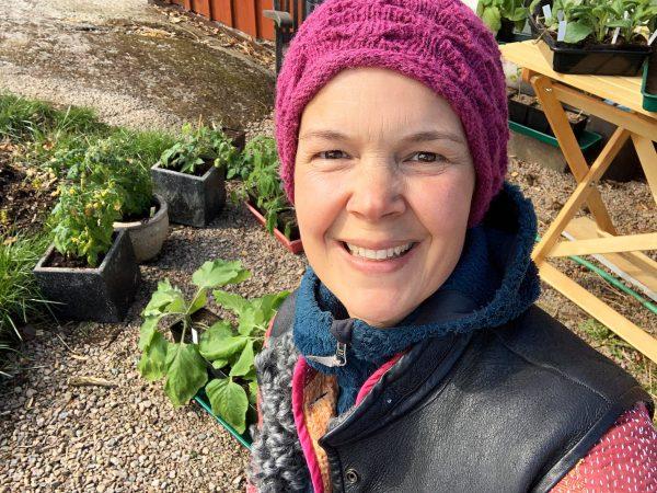 En glad Sara i lila mössa står i köksträdgården