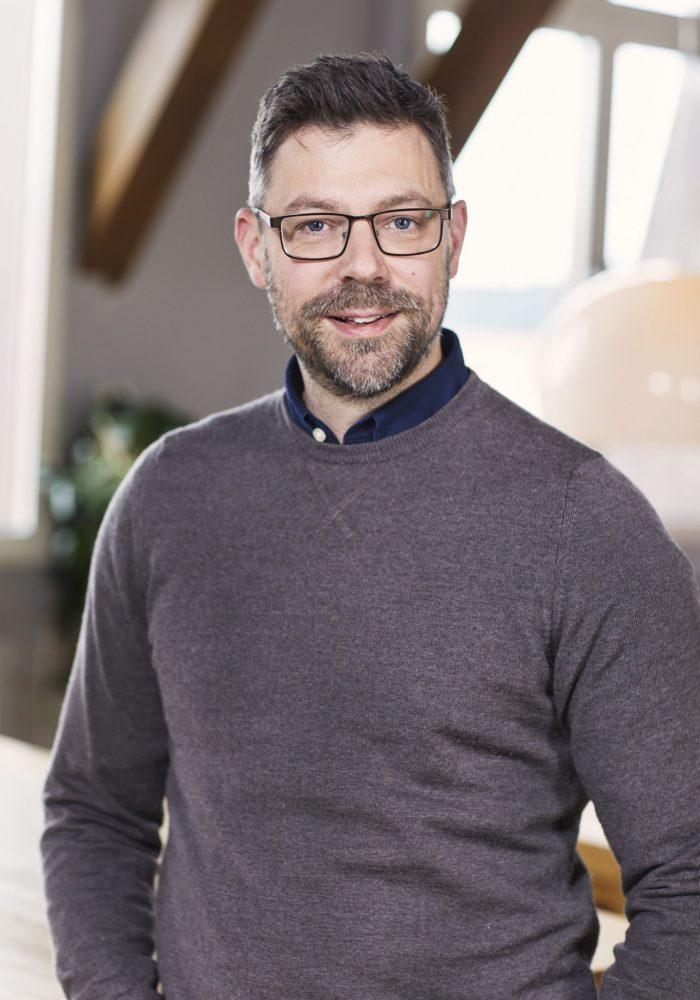 Porträttbild av en man med glasögon och kort hår.