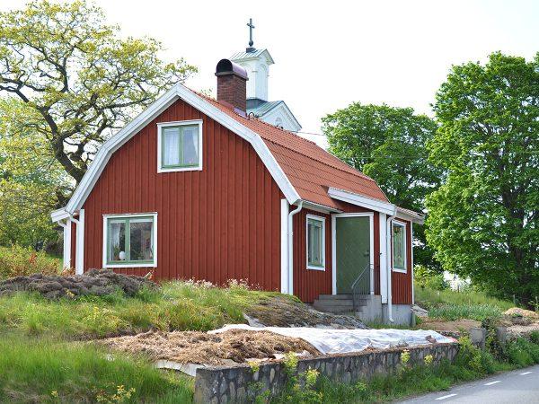 En rött hus på landet med köksträdgård på framsidan