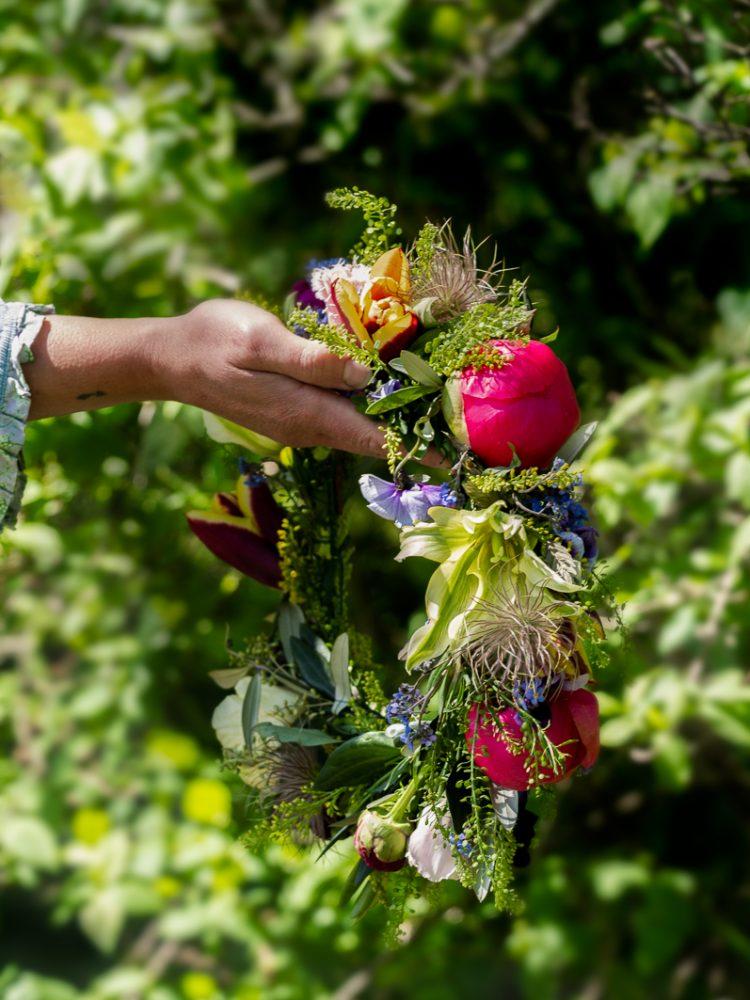 En hand håller en blomkrans
